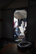 A Kurdish family from Syria is gathered beside a fire outside their shelter at Kara Tepe camp near Mytilene, Lesbos, Greece. The camp was established for refugees transiting through Lesbos on their way from Turkey to the heart of Europe. An intertube, bought for the dangerous boat trip from Turkey, sits inside the entrance.