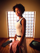An african-american woman enjoys her morning yoga at home on her hardwood floors