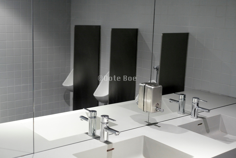 clean male toilet room with mirror and hands washing sink