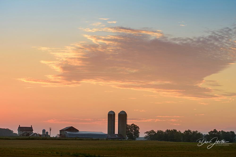 Farm buildings with silos at dawn, Wonderland Road, near London, Ontario, Canada