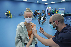 """© Licensed to London News Pictures. 03/07/2021. Sheffield, UK.. Lucy Holcroft ,18 ,receives the first dose of the Pfizer/BioNTech vaccine at a pop-up vaccination clinic at Hillsborough Stadium in Sheffield as part of the """"Grab a jab"""" campaign. Photo credit: Ioannis Alexopoulos/LNP"""