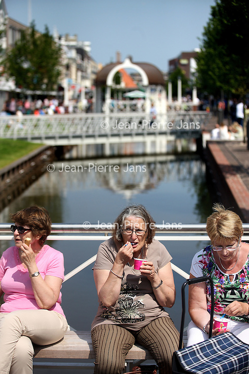 Nederland, Zaandam , 6 juli 2013.<br /> Wandeling door de binnenstad van Zaandam.<br /> Starten bij De Werf aan de Oostzijde. Daarvandaan kun je lopen op een soort boulevard tussen de flats en het water. De eerste stop is De Fabriek, filmhuis en eetcafé met terras aan de Zaan met uitzicht op de sluis. Daarna de sluis zelf.<br /> Dan langs het winkelgebied richting de Koekfabriek: Het oude Verkade pand dat is verbouwd en waar nu de bieb en sportschool en restaurant etc. in zitten.<br /> (Dat is aan de overkant van het startpunt) en misschien nog de Zwaardemaker meepakken aan de Oostzijde. Dat is een oud pakhuis die Rochdale enige jaren geleden heeft verbouwt tot appartementen met een stukje Nieuwbouw.<br /> Ook doen: het Russische buurtje vlakbij de Zaan. Dit jaar staat Rusland in de schijnwerpers en Zaandam heeft een speciale band met Rusland, vanwege het Czaar Peterhuisje en de Russische buurt. <br /> Op de foto: lekker ijsje eten boven de gedempte gracht.<br /> Foto:Jean-Pierre Jans