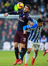 Arsenal's Sead Kolasinac (left) and Huddersfield Town's Christopher Schindler battle for the ball during the Premier League match at the John Smith's Stadium, Huddersfield.