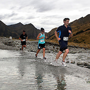 Runners Cameron Stewart (left) Pru Renshaw and Edward Styles (right)  cross Moke Creek on the Ben Lomond High Country Station during the Pure South Shotover Moonlight Mountain Marathon and trail runs. Moke Lake, Queenstown, New Zealand. 4th February 2012. Photo Tim Clayton