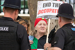 London, August 23rd, 2014. A woman chats with police officers as hundreds of pro- Palestine protesters demonstrate outside Downing Street demanding that Britain stops arming Israel.