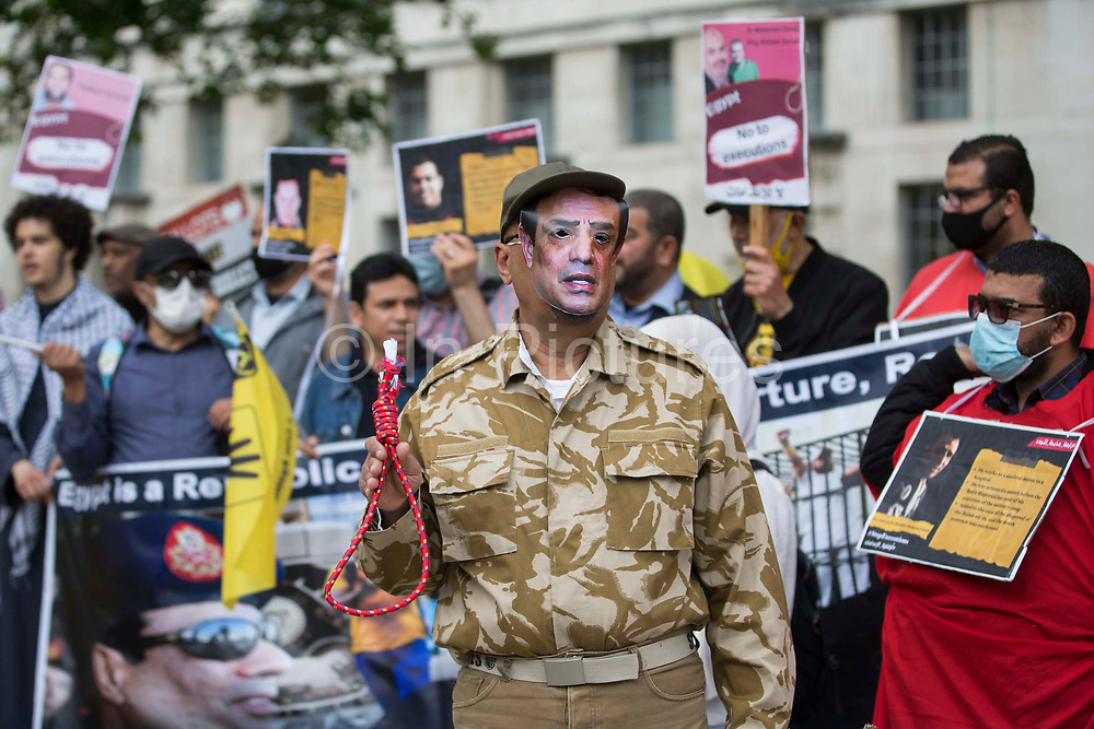 A man wearing a mask featuring an image of General Abdel Fattah el-Sisi and holding a noose stands in front of anti-coup activists protesting opposite Downing Street against political executions in Egypt on the 8th anniversary of the Egyptian military coup against President Mohamed Morsi on 3rd July 2021 in London, United Kingdom. 92 political prisoners have been executed in Egypt since the coup, with death sentences ratified by General Abdel Fattah el-Sisi for a further 64.