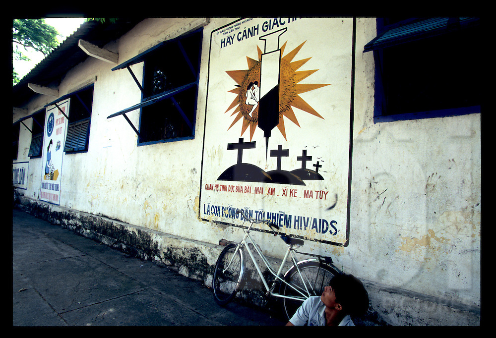 A young vietnamese man looks at a propaganda style poster warning about AIDS spread disease through syringe usage, Can Tho, Vietnam, Southeast Asia, 1997