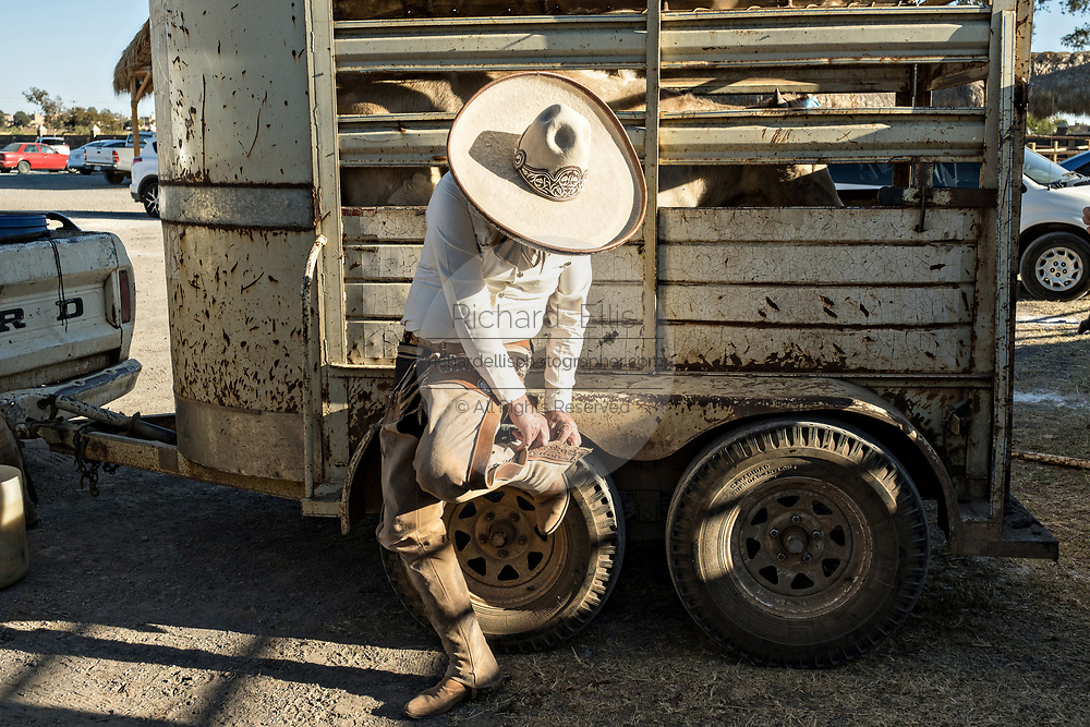 Juan Franco, Sr., buttons his chaps as he dresses in the traditional Charro costume as he readies for a family practice session in the Jalisco Highlands town of Capilla de Guadalupe, Mexico. The Franco family has dominated Mexican rodeo for 40-years and has won three national championships, five second places and five third places.