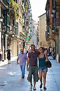 Young couple stroll arm in arm in Calle de Bidebarrieta in Bilbao, Spain