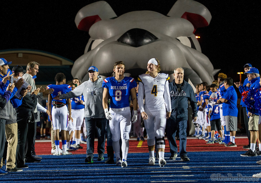 Folsom High School Bulldogs Brad Jenner (8), is joined by his brother Oak Ridge Trojans Matt Jenner (4), as he walks out during senior night before the game as the Folsom High School Bulldogs varsity football team host the Oak Ridge High School Trojans,  Friday Nov 4, 2016.<br /> photo by Brian Baer