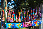 Brightly coloured souvenirs and gifts - handbags, towels with maps -  hanging up for sale at stall at Paleokastritsa, Corfu, Greece