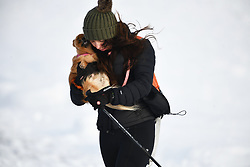 © Licensed to London News Pictures. 04/12/2020. <br /> A women protects her dog against the wind as she walks on Penyfan, in the Brecon Beacons, the highest point in southern Wales and England, which has seen it's first snowfall of the year. Photo credit: Robert Melen/LNP