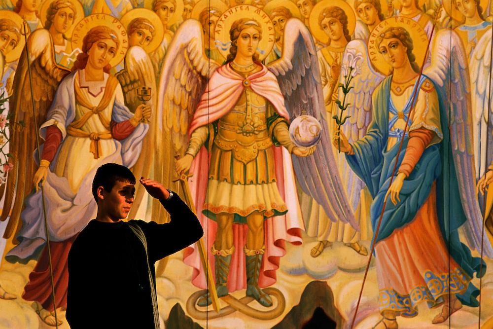 Ucrania. Kiev<br /> Un joven se protege del sol delante del mural de la fachada de la Catedral de Mijailovsky.<br /> Ukraine. Kiev. <br /> Mural at the façade of the Cathedral of Mijailovsky.<br /> <br /> © JOAN COSTA