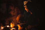 A woman lighting incense sticks to be given as an offering at a Hindu shrine, River Ganges, Varanasi, India