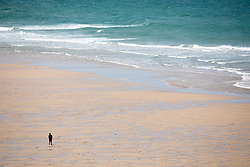 """© Licensed to London News Pictures. 11/05/2020. Newquay, UK. A man walks along Watergate Bay beach on the North coast of Cornwall, the day after British Prime Minister Boris Johnson announced a 'road map' to lift lockdown restrictions due to Covid-19, (Coronavirus). A rise in """"staycations"""" - the concept of holidaying in your home country rather than travelling abroad - is expected, with many visitors planning to visit Cornwall. However, an ongoing campaign titled """"#ComeBackLater"""" is trying to persuade tourists not to visit the county until it is safe to do so. Photo credit : Tom Nicholson/LNP"""