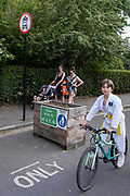A young cyslist passes through the barriers that form an LTN (Low Traffic Neighbourhood), an experimental closure by Southwark Council preventing motorists from accessing the junction of Carlton Avenue and Dulwich Village. Restrictions also prevent traffic from passing through at morning and afternoon rush-hour times in the borough of Southwark, on 14th June 2021, in London, England.