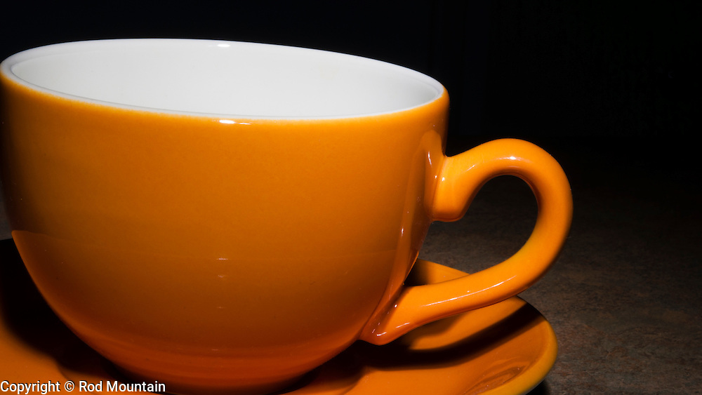 Empty orange coffee cup with saucer.