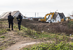 © London News Pictures. Calais, France. 18/01/16. French CRS national police stand in front of diggers brought in to clear around 1/3 of the Calais 'Jungle'. French authorities are clearing a 100-metre 'buffer zone' between the camp and the adjacent motorway, which leads to the ferry port.  Photo credit: Rob Pinney/LNP
