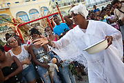 Cuban woman of African descent throwing rice to the crowd in a traditional gesture. Performance in Havana old town, local dance and theatre group enacting the slave trade, colonial rule and how African religion and beliefs continuing, becoming what is now Santeria.