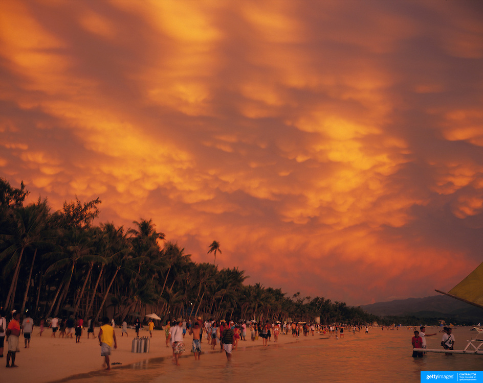 Asian tourists during an amazing sunset at White Beach,  Boracay Island, the Philippines on October 7, 2008, Photo Tim Clayton..Asian tourists at White Beach, Boracay Island, the Philippines...The 4 km stretch of White beach on Boracay Island, the Philippines has been honoured as the best leisure destination in Asia beating popular destinations such as Bali in Indonesia and Sanya in China in a recent survey conducted by an International Travel Magazine with 2.2 million viewers taking part in the online poll...Last year, close to 600,000 visitors visited Boracay with South Korea providing 128,909 visitors followed by Japan, 35,294, USA, 13,362 and China 12,720...A popular destination for South Korean divers and honeymooners, Boracay is now attracting crowds of tourists from mainland China who are arriving in ever increasing numbers. In Asia, China has already overtaken Japan to become the largest source of outland travelers...Boracay's main attraction is 4 km of pristine powder fine white sand and the crystal clear azure water making it a popular destination for Scuba diving with nearly 20 dive centers along White beach. The stretch of shady palm trees separate the beach from the line of hotels, restaurants, bars and cafes. It's pulsating nightlife with the friendly locals make it increasingly popular with the asian tourists...The Boracay sailing boats provide endless tourist entertainment, particularly during the amazing sunsets when the silhouetted sails provide picture postcard scenes along the shoreline...Boracay Island is situated an hours flight from Manila and it's close proximity to South Korea, China, Taiwan and Japan means it is a growing destination for Asian tourists... By 2010, the island of Boracay expects to have 1,000,000 visitors.