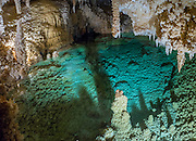 """Halo Lake is an attractive green pool of water in Caverns of Sonora, Sutton County, Texas, USA. The world-class Caverns of Sonora have a stunning and sparkling array of speleothems (helictites, stalactites, stalagmites, flowstone, coral trees, and other calcite crystal formations). National Speleological Society co-founder, Bill Stephenson said, after seeing it for the first time, """"The beauty of Caverns of Sonora cannot be exaggerated...not even by a Texan!"""" Geologically, the cave formed between 1.5 to 5 million years ago within 100-million-year-old (Cretaceous) Segovia limestone, of the Edward limestone group. A fault allowed gases to rise up to mix with aquifer water, making acid which dissolved the limestone, leaving the cave. Between 1 and 3 million years ago, the water drained from the cave, after which speleothems begain forming. It is one of the most active caves in the world, with over 95% of its formations still growing. Sonora Caves are on Interstate 10, about half-way between Big Bend National Park and San Antonio, Texas. This panorama was stitched from 2 overlapping photos."""