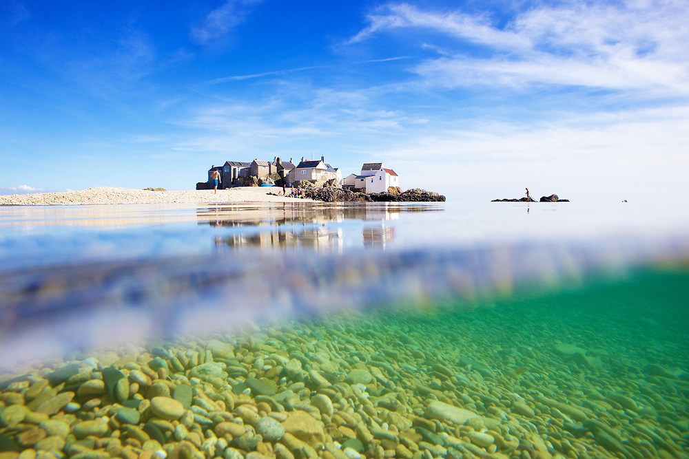 View of the houses on the beach at the Ecrehous from under the glassy calm sea water on a sunny day in Jersey, Channel Islands