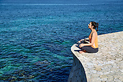 Woman practicing oceanfront yoga meditation.
