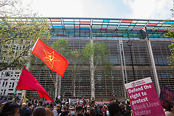London, UK. 1st May, 2021. A man holds a Communist flag outside the Home Office during a Kill The Bill demonstration as part of a National Day of Action on International Workers Day. Nationwide protests have been organised against the Police, Crime, Sentencing and Courts Bill, which would grant the police a range of new discretionary powers to shut down protests.