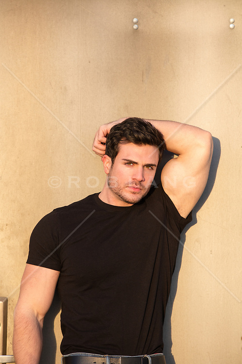 sexy hunky man against a wall at sunset