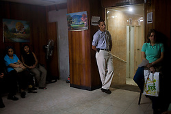 Julio Rodriguez, a sales rep for Pfizer, waits to make a sales call at a clinic in Petare, one of the largest and most dangerous slums of Caracas. Pfizer is trying to increase their market share in the slums and are targeting clinics, hospitals and pharmacies, sending sales representatives to the far reaches of the slum.