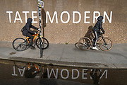 Two young black men ride their bikes past Brutalist concrete architecture Tate Modern art gallery on the Southbank, on 26th October 2020, in London, England.