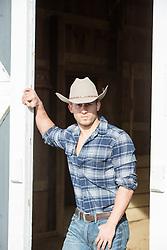 handsome cowboy by a barn
