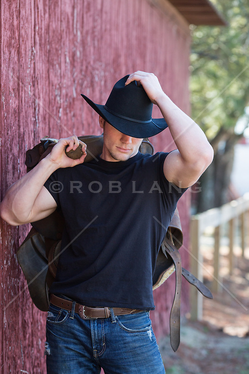 cowboy with a saddle over his shoulder walking by a barn