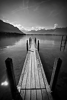 Black and white photo of a pier overlooking scenic Lake Geneva in Montreux, Switzerland.