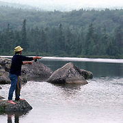 A man fly fishing in Sandy Stream Pond, Baxter State Park, Maine, USA