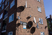 Satellite dishes on the side of a block of flats in a south London estate. The receivers have been bolted to the brick at the end of this block's outer wall, their shadows forming a pattern of dark circles. The flats are in Camberwell, in the south London borough of Southwark.