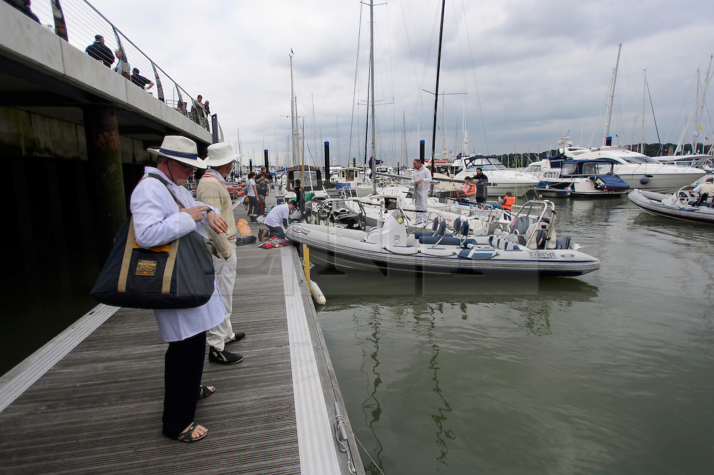 © Licensed to London News Pictures. 18/09/2016. Portsmouth, UK. The umpire checks his watch as he waits for his boat to collect him to take him to the match. Teams take part in the  Bramble Bank Cricket Match in the middle of The Solent strait on September 18, 2016. The annual cricket match between the Royal Southern Yacht Club and The Island Sailing Club, takes place on a sandbank which appears for 30 minutes at lowest tide. The game lasts until the tide returns. Photo credit: Ben Cawthra/LNP