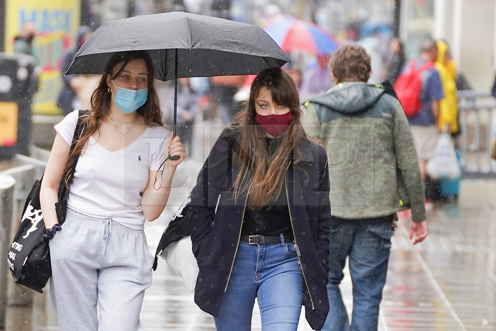 © Licensed to London News Pictures. 28/08/2020. Manchester. Shoppers shelter under an umbrella  during  heavy rainfall this morning in Manchester. Photo credit: Ioannis Alexopoulos/LNP