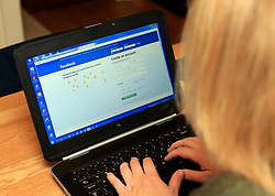PICTURE POSED BY MODEL<br /> A woman logs into her Facebook account as one billion people have used the social networking site in a single day for the first time in the site's 11-year history.