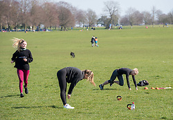 © Licensed to London News Pictures; 22/03/2020; Bristol, UK. Coronavirus Pandemic; people exercise in the open air on Bristol's Downs on a sunny weekend, after the UK's prime minister ordered the closure of all pubs, bars, cafes, restaurants and indoor gyms to try and prevent the spread of the coronavirus. The UK Government is urging people to maintain social distance but also to get fresh air and exercise outside with social distance between people. Photo credit: Simon Chapman/LNP.