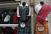 Tartan kilts and national Scots fabrics on sale in the window of a tourist shop on the Royal Mile in Edinburgh, on 25th June 2019, in Edinburgh, Scotland.