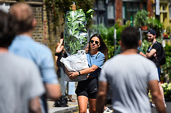 © Licensed to London News Pictures. 05/07/2020. LONDON, UK.  A girl carries her purchase as plant lovers visit Columbia Road Flower Market in East London on the its reopening after certain coronavirus pandemic lockdown restrictions were relaxed by the UK government.  Photo credit: Stephen Chung/LNP