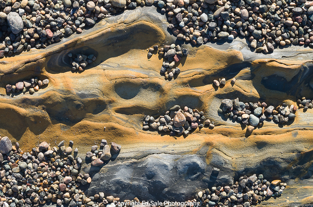Pebbles partially cover wave-worn rusty-yellow-colored rock in the tidal zone at Weston beach, Point Lobos State Park, California