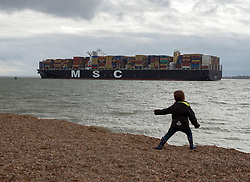 © Licensed to London News Pictures. 06/04/2014. Felixstowe, UK. A young boy throws stones into the sea as a container ship departs port.  People under cloudy and windy conditions on the shoreline at Felixstowe today 6th April 2014. Photo credit : Stephen Simpson/LNP