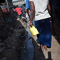 Residents walk along streams of polluted water down the side streets of Mathare.