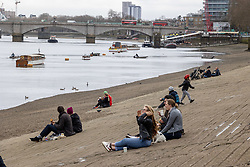 """© Licensed to London News Pictures. 28/03/2021. London, UK. Members of the public relax along the River Thames in Putney, South West London ahead of the end of the """"Stay at Home"""" advice from tomorrow with temperatures expecting to reach up to 23c next week. On Monday 29 March, the """"Stay at Home"""" advice will end with people being allowed to meet up within the """"rule of six"""". Playing golf, tennis and organised outdoor sports will also be allowed as England starts to unlock after a year of Covid-19 restrictions. Photo credit: Alex Lentati/LNP"""