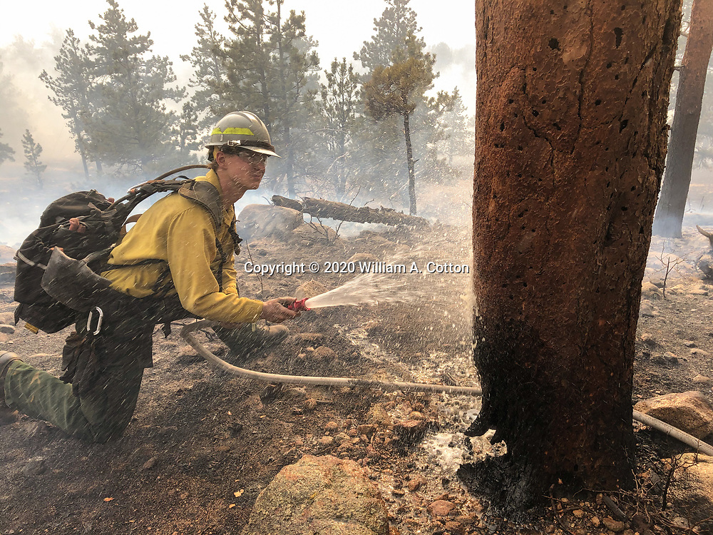Larimer County Sheriff's Office firefighter Quinn de la Haye cools down a burning tree near a structure north of Moraine Park in Rocky Mountain National Park, October 24, 2020 as the East Troublesome Fire burns in the park. © 2020 William A. Cotton