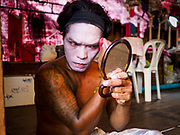 """26 FEBRUARY 2018 - BANGKOK, THAILAND: Performers put on their makeup before a Chinese Opera at the Phek Leng Shrine in the Khlong Toey section of Bangkok. The shrine traditionally hosts a Chinese Opera just after the end of Lunar New Year festivities. Thailand is home to the largest population of overseas Chinese in the world, and Chinese cultural practices, like Chinese opera, called """"ngiew"""" in Thailand, are popular. Many of the performers are ethnic Thais who don't speak Chinese. They learn their lines phonetically.     PHOTO BY JACK KURTZ"""