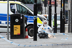 © Licensed to London News Pictures. 11/10/2019. Manchester, UK. Forensic scenes of crime examiners document the contents of a bin in front of the entrance to the Arndale Centre . Terrorism Police are investigating after four people were stabbed during a single attack at the Arndale Centre in Manchester City Centre . Photo credit: Joel Goodman/LNP