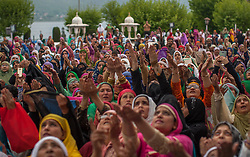 April 25, 2017 - Srinagar, Jammu and Kashmir, India - Kashmiri Muslim women pray as a head priest displays the holy relic believed to be the whisker from the beard of the Prophet Mohammed on the occasion of the Muslim festival Mehraj-u-Alam, which marks ascension day, the journey from earth to heavens of the Prophet Mohammed, at the Hazratbal Shrine on April 25, 2017 in Srinagar, the summer capital of Indian administered Kashmir, India. Every year thousands of Muslim devotees from across Kashmir throng the Hazratbal shrine in central Srinagar for prayers to have a glimpse of the Moi-e-Muqaddas, Holy Relic of Prophet Mohammed, displayed for public viewing on ten occasions in a year , including Meraj-ul Alam , the night Muslims believe Prophet Mohammed ascended to the heaven. (Credit Image: © Yawar Nazir via ZUMA Wire)